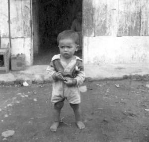 Profil Sjaya-anak ke 8 delapan) Rophian Sembiring tahun 1952 di depan rumah petak dinding papan atap seng yang dikontrakan